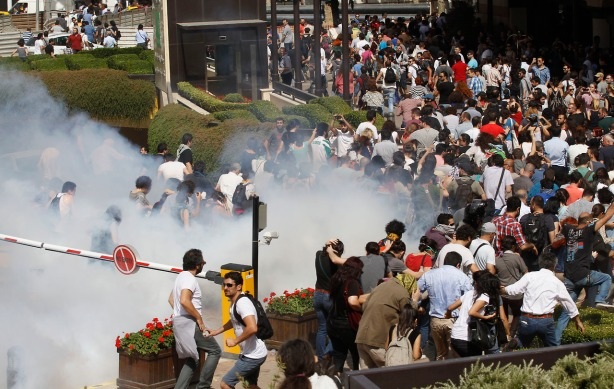 Turkish riot police use tear gas to disperse demonstrators during protest against destruction of trees in park brought about by pedestrian project, in Taksim Square in central Istanbul